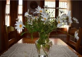 Mesa de comedor con florero y margaritas de la masía