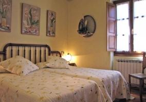 Dormitorio con dos camas y butaca