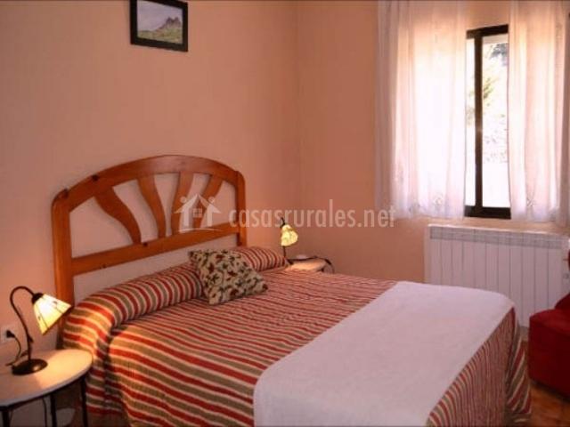 Dormitorio con cama de matrimonio y pared rosa