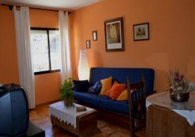 Sala de estar con televisor frente a sillón azul