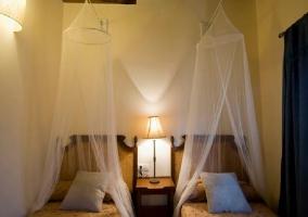 Dormitorio con camas individuales con mosquitera