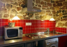 Cocina del alojamiento con azulejos rojos