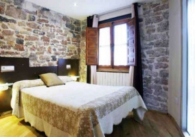 Dormitorio con cama doble y pared de piedra