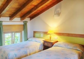 Dormitorio de matrimonio con vigas de madera en el techo