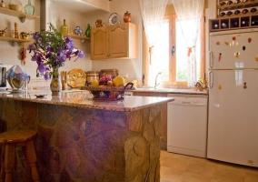 Amplia cocina con barra americana de piedra