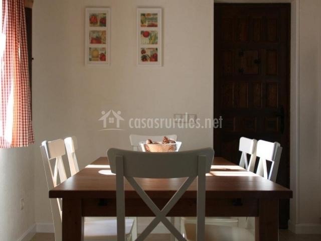 Comedor con mesa de madera y sillas blancas