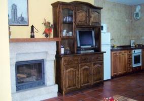 Sala de estar con chimenea y cocina al lado