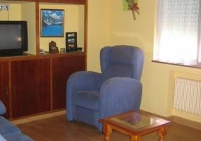 Sala de estar con televisor y sillones azules