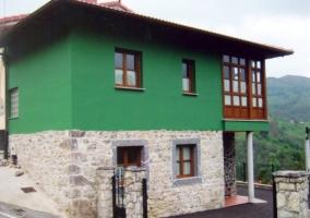 Vista exterior del edificio con muros de piedra y verdes