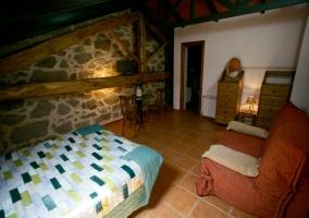 Dormitorio con cama doble y paredes de piedra