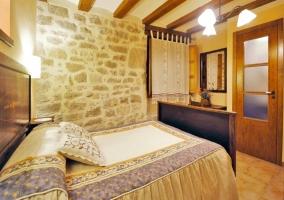 Dormitorio de matrimonio con cabecero de madera antiguo
