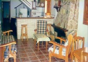 Sala de estar con chimenea y cocina con barra americana