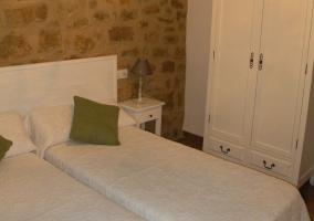 Habitación con dos camas, muebles blancos y balcón