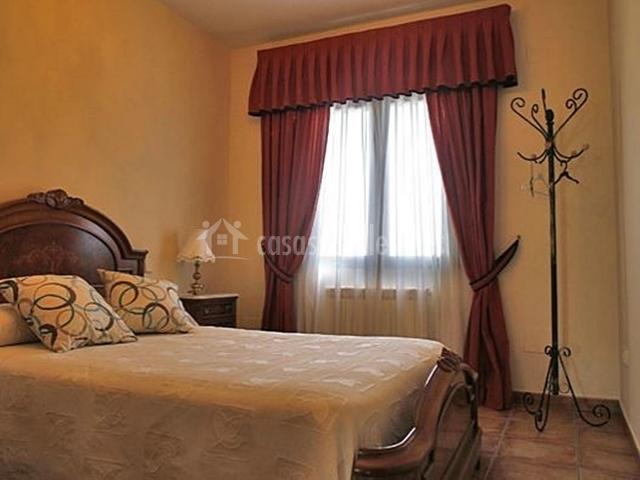 Dormitorio con cabecero de madera trabajada