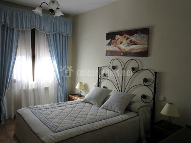 Habitación de matrimonio con cortinas en azul
