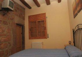 Dormitorio de matrimonio con TV y pared de piedra