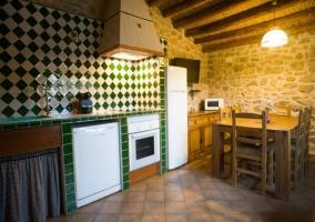 Cocina con office y techos de madera