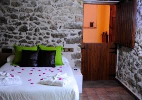 Dormitorio matrimonio con muro de piedra y baño