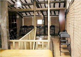 Sala con sillas negras y techo con vigas de madera