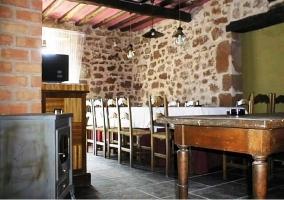 Salón comedor con mesa y pared de piedra