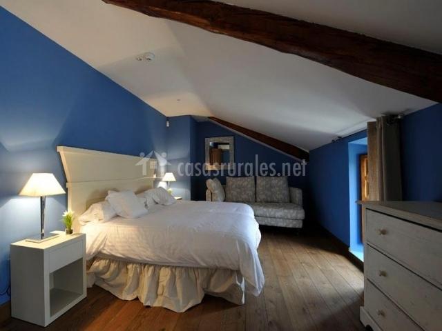 Dormitorio abuhardillado de matrimonio con pared azul