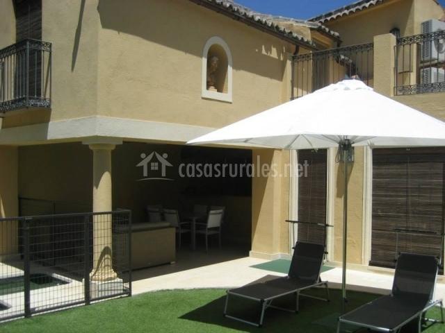 Hamacas con sombrilla junto a porche y piscina
