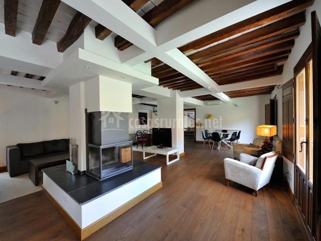 Salón comedor con chimenea central y vigas de madera