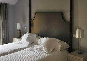 Dormitorio doble con cabecero y paredes grises