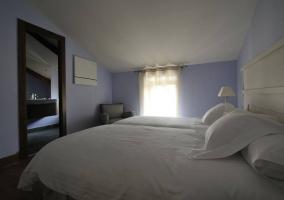 Dormitorio doble lila con techo abuhardillado y baño