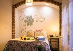 Cama de dormitorio con mesilla, ventana con cortinas y decoración