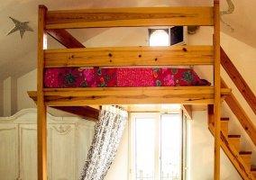Cama alta/litera en dormitorio con balcón