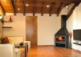 Hall de entrada del alojamiento rural con muebles de madera tallada paredes de piedra y suelo de baldosas de barro cocido