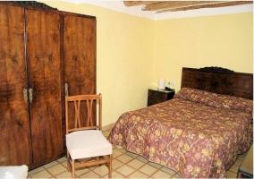 Dormitorio de matrimonio de la casa rural con armario de madera.