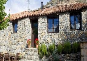 Vista de la finca, fachada de la vivienda y jardín con jacuzzi