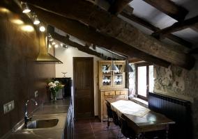 Chimenea encendida en el salón con vistas a la cocina comedor