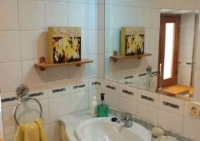 Aseo con espejo grande sobre el lavabo