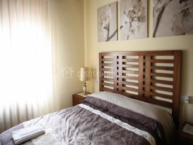 Dormitorio de matrimonio con cabecero moderno de madera