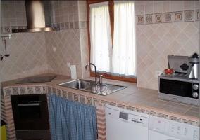 Cocina abierta con electrodomésticos. Muro de ladrillo y vigas de madera