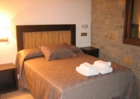 Habitación matrimonial con pared de piedra vista