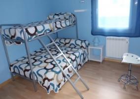 Dormitorio en tonos azules con una litera incluida