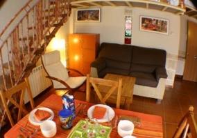 Salón comedor con moderna televisión y escalera al piso superior