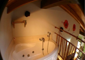 Dormitorio de matrimonio en el piso superior, con vistas al salón comedor y la cocina, y relajante bañera hidromasaje