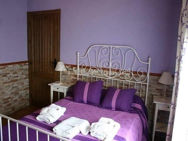 Dormitorio de matrimonio, entre paredes y ropa morada