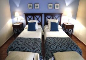 Dos camas individuales con pared del fondo de color azul