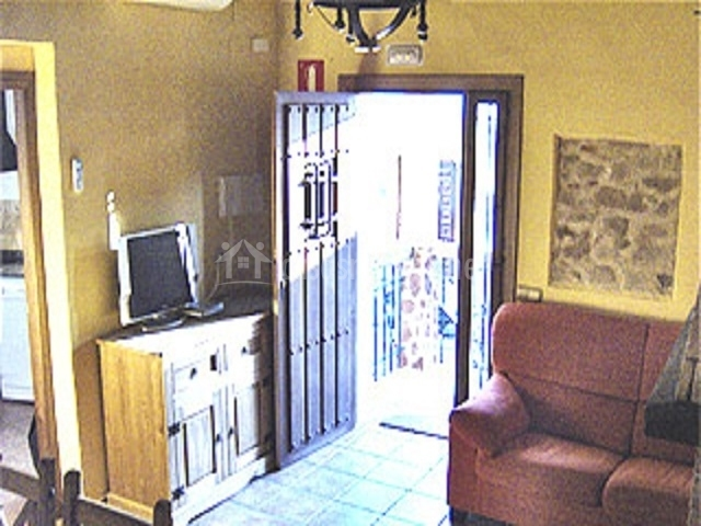 Entrada a la casa, salón con moderna televisión