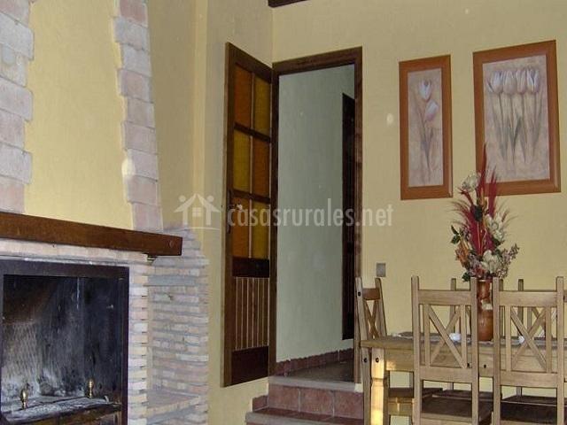 Comedor delante de la chimenea con escaleras al interior de la casa