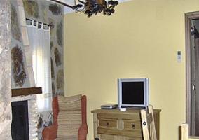 Butaca, moderna televisión y mesa de comedor alrededor de la chimenea