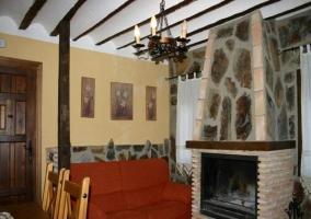 Salón con cómodo sofá y bonita chimenea de piedra