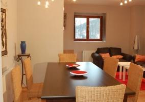 Sala de estar con sillones de cuero negros y escaleras