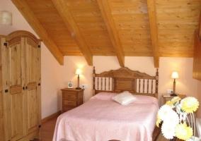 Dormitorio de matrimonio abuhardillado con techo de mader
